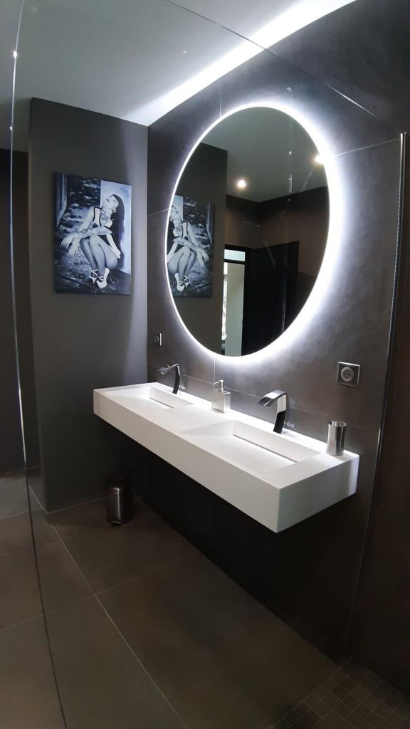 salle de bain design noire et blanche avec miroir rond