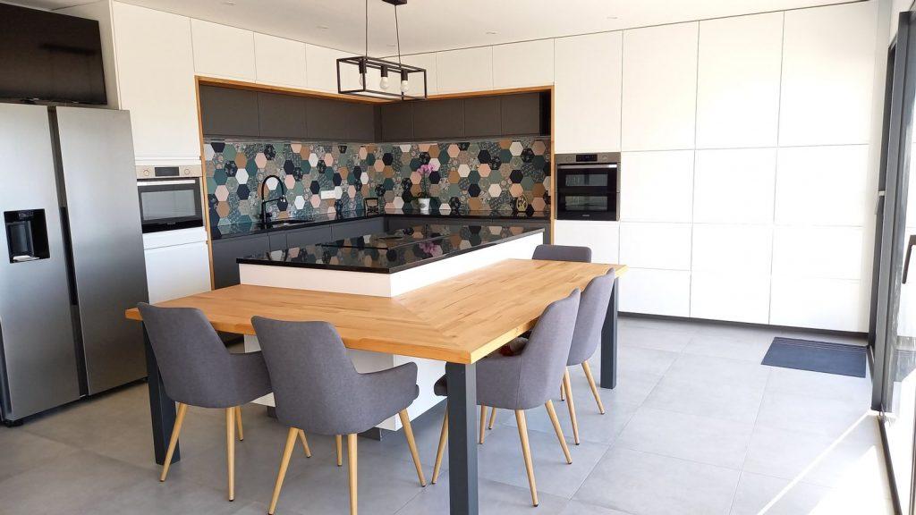 Une cuisine d'angle moderne blanche et noire avec crédence colorée