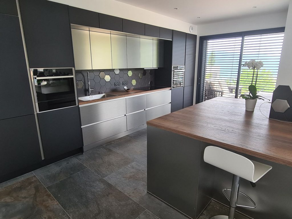 Une grande cuisine aménagée ultra-moderne noire et inox