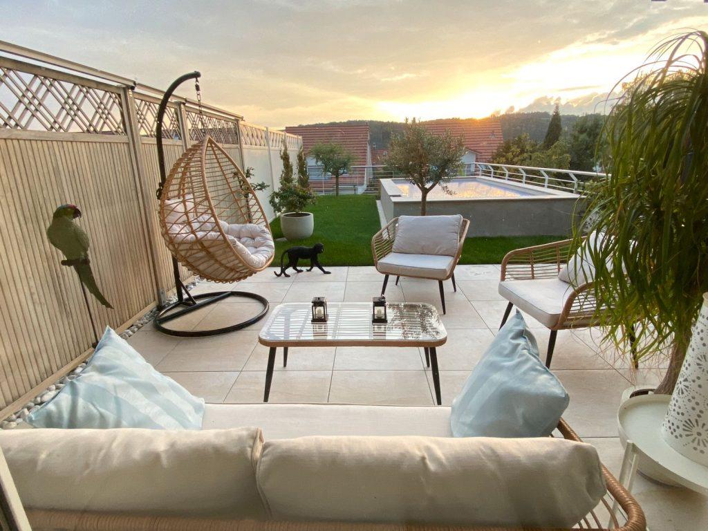 terrasse exotique sur-élevée avec salon de jardin en rotin