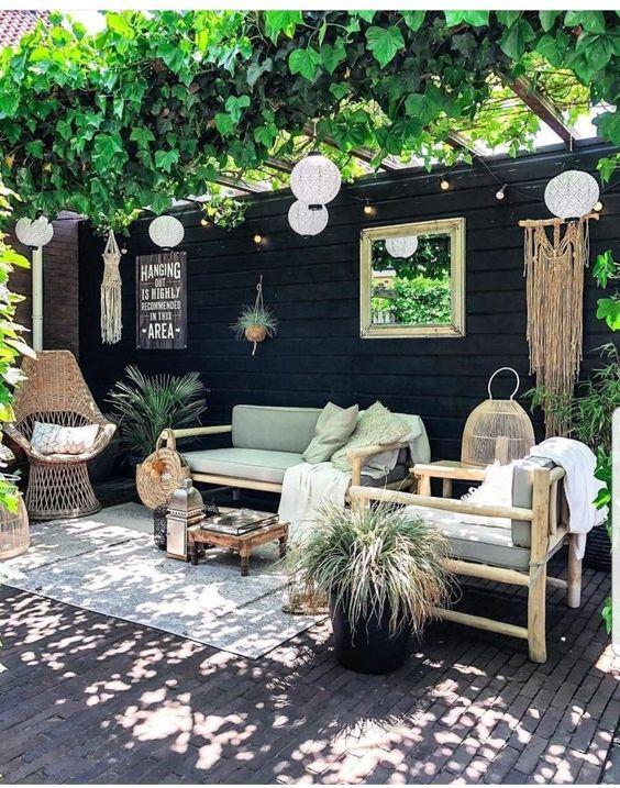 Un coin terrasse nature avec des plantes et suspensions lumineuses