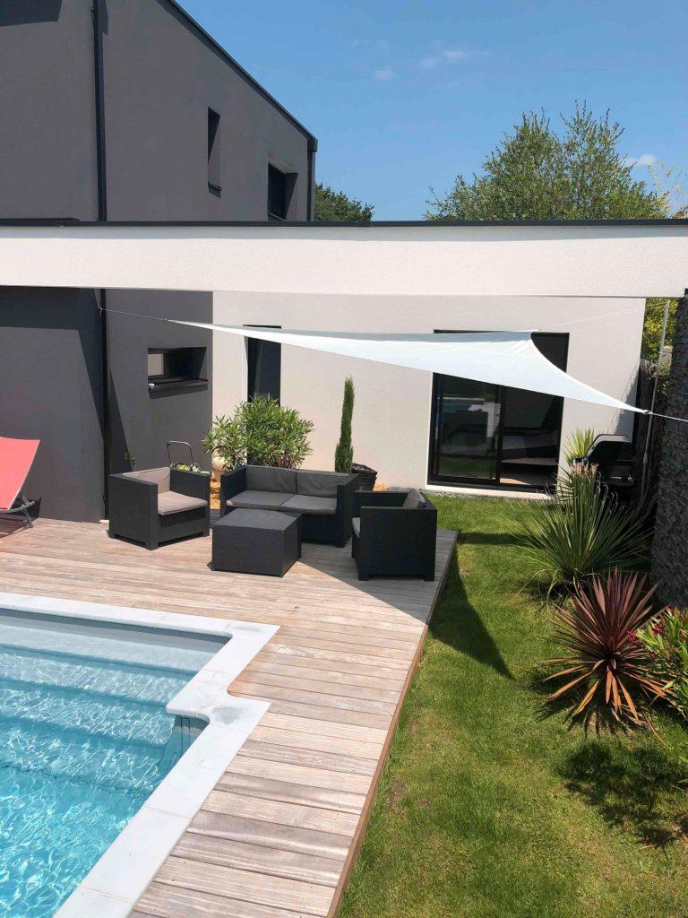 maison design avec salon de jardin moderne et voile d'ombrage sur la terrasse