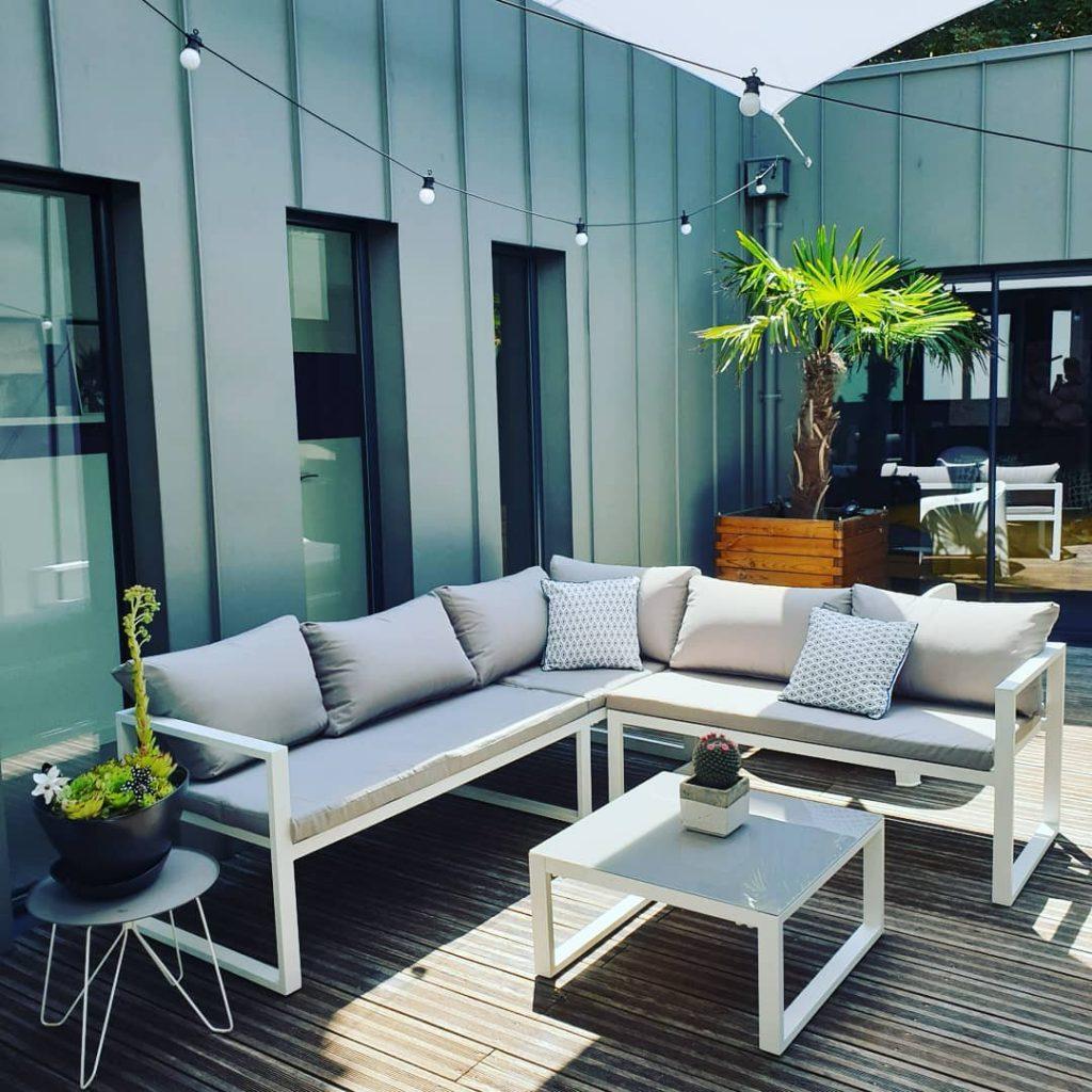 patio loft industriel avec salon de jardin moderne et palmiers